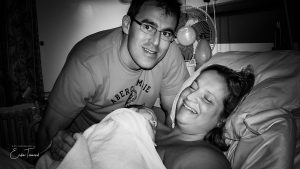 Black and white image of a couple holding their newborn baby after giving birth in hospital