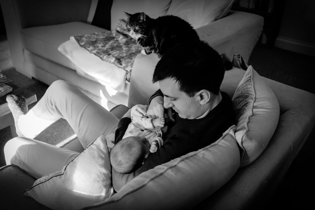Black and white image of a new father holding his daughter at home in the post natal period