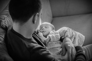 Black and white image of Dad and Newborn at home in the post natal period