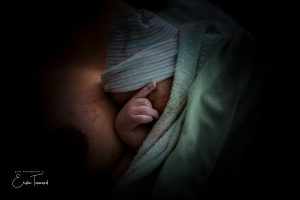 Colour photo of newborn covering their faces