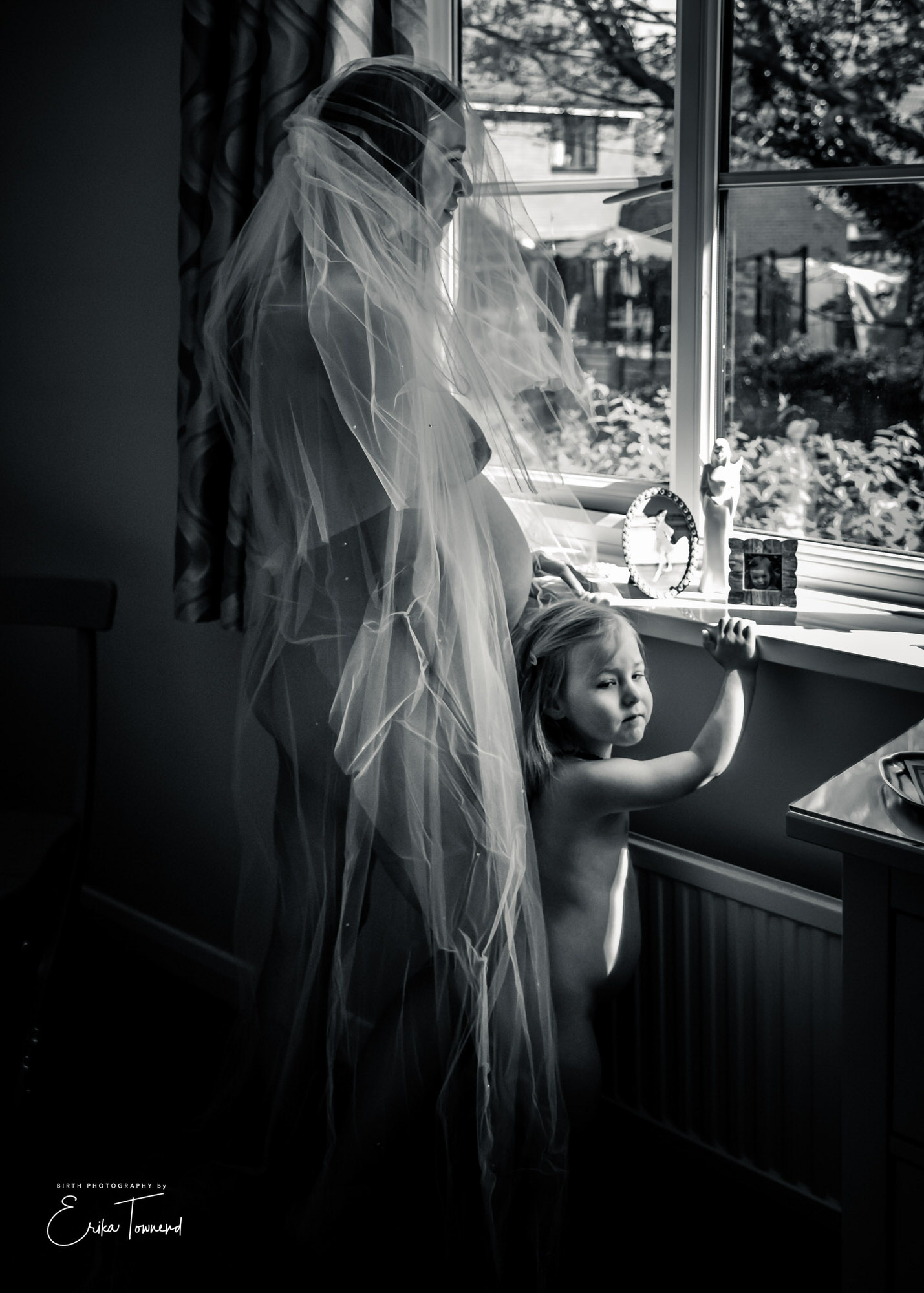 Black and white image of pregnant woman standing by her window in her wedding veil and young daughter