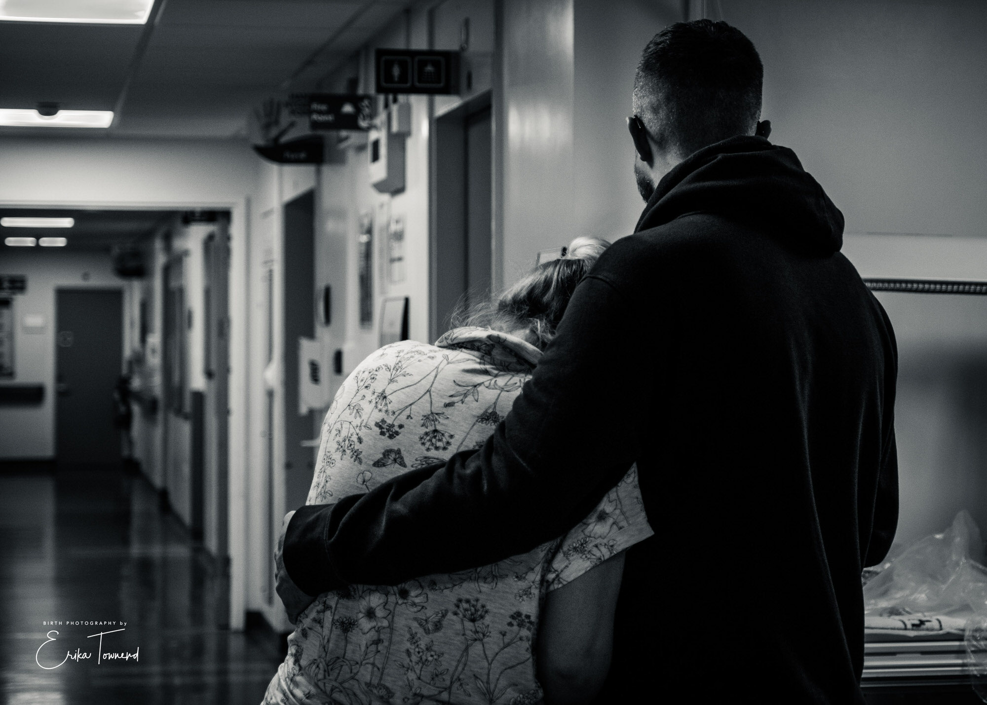 Black and white image of a couple in labour in hospital woman being comforted by Erika Townend Birth