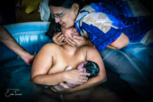 Colour image of a mother hugging her daughter greeting their newborn baby