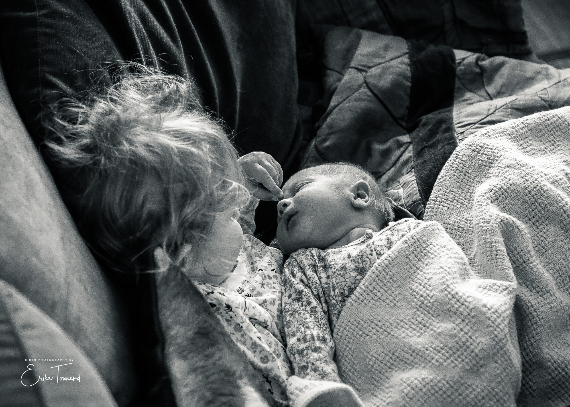 Documentary black and white image of newborn with big sister touching her new sisters nose