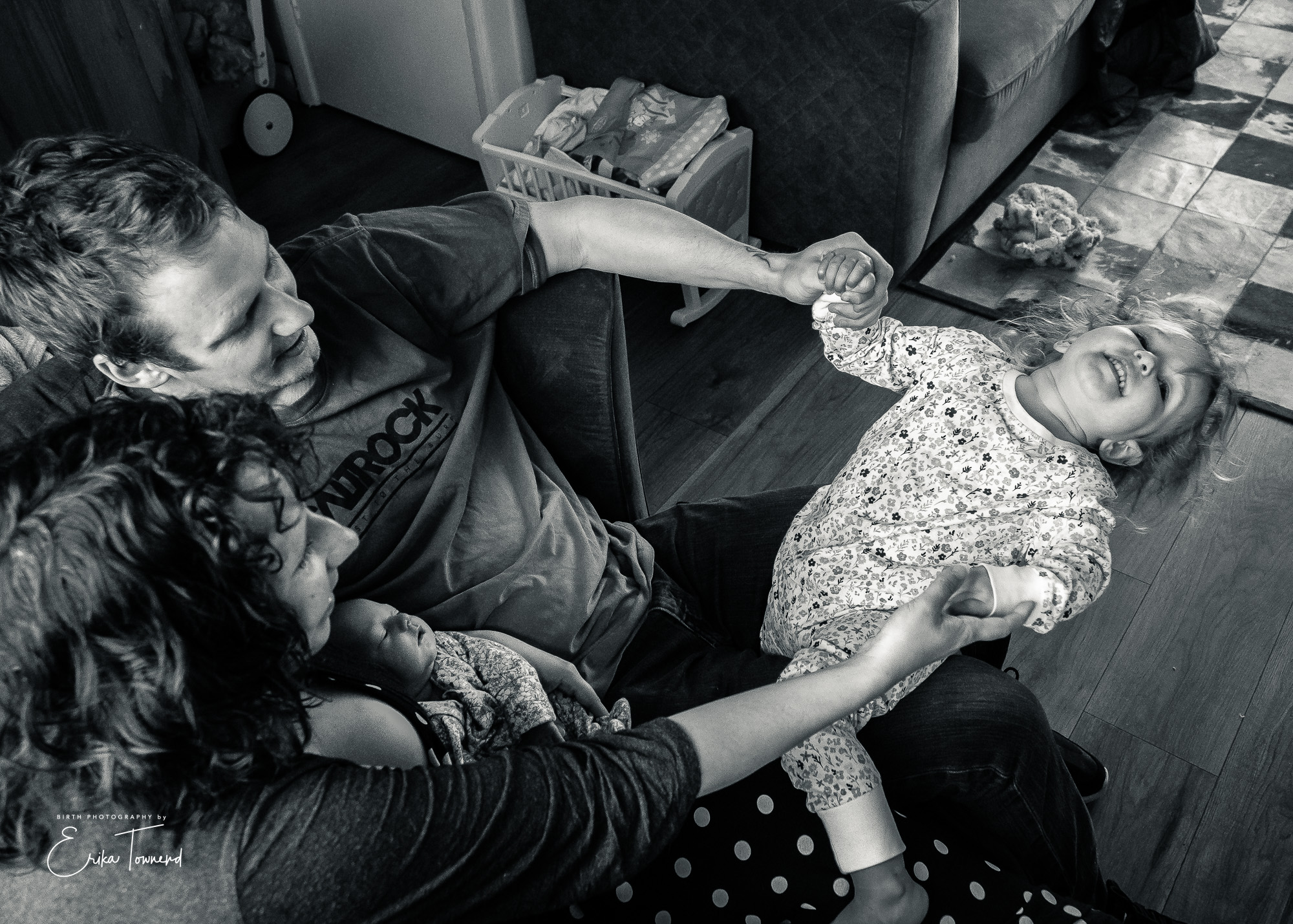 Documentary black and white image of having fun playing row row my boat with their eldest and their newborn in their laps fast asleep